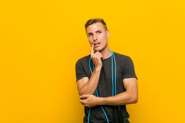 El hombre caucásico joven que sostenía una comba se relajó pensando en algo que miraba un espacio de la copia. Foto Premium