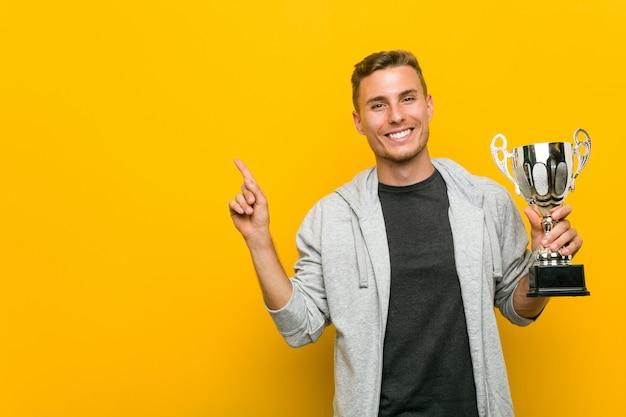 Hombre caucásico joven que sostiene un trofeo que sonríe alegremente que señala con el índice lejos. Foto Premium