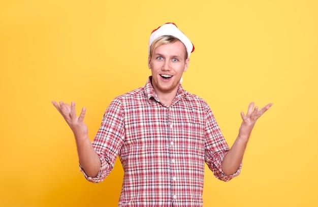 Hombre caucásico de navidad sorprendido que cubre la boca con las manos aisladas sobre fondo amarillo brillante. Foto Premium