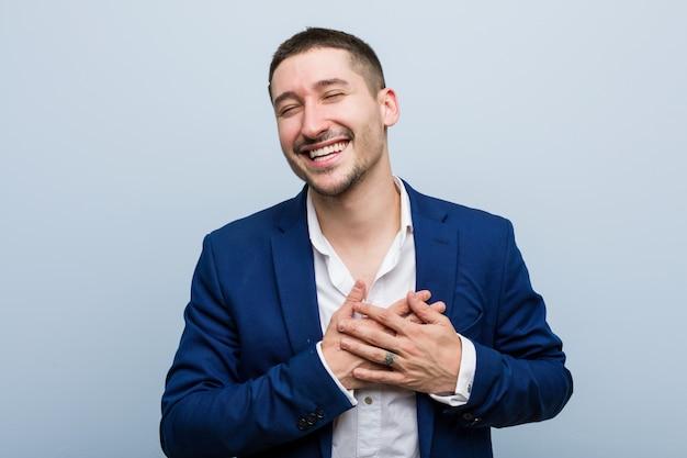 Hombre caucásico de negocios joven riendo manteniendo las manos en el corazón, de la felicidad. Foto Premium