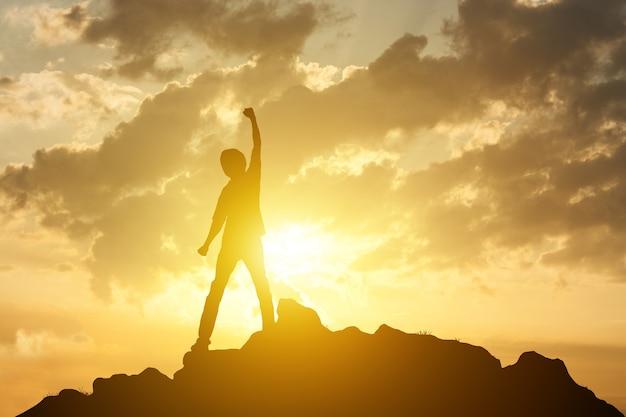 Hombre en la cima de la montaña y el concepto de éxito de ganador de fondo de amanecer o puesta de sol Foto Premium