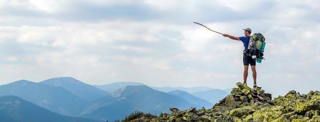 Hombre en la cima de la montaña. escena emocional hombre joven con mochila Foto Premium