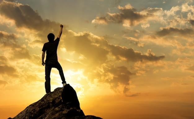 Hombre en la cima de la montaña y la luz del sol, éxito, concepto de ganador Foto Premium