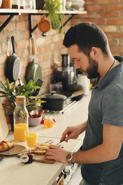Hombre cocinando en la cocina. desayuno por la mañana Foto gratis