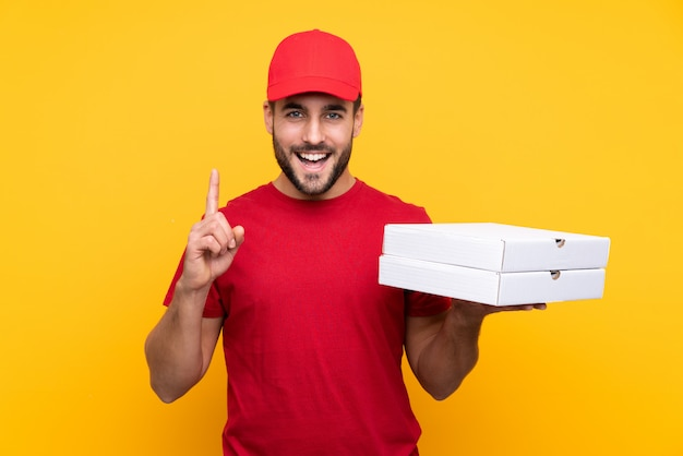 Hombre cogiendo cajas de pizza sobre pared aislada Foto Premium
