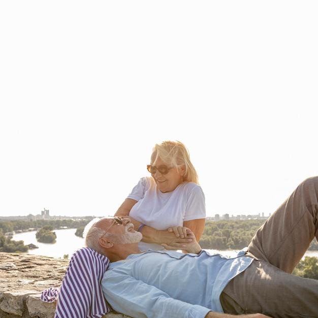 Hombre colocando su cabeza sobre las piernas de la mujer Foto gratis