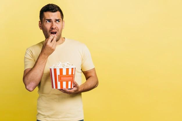 Hombre comiendo palomitas de maíz con espacio de copia Foto gratis