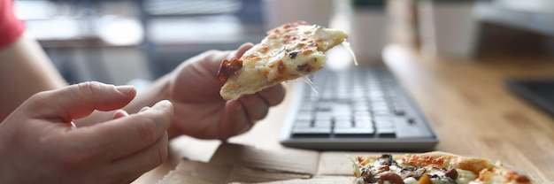 Hombre comiendo pizza en el lugar de trabajo frente a la computadora Foto Premium