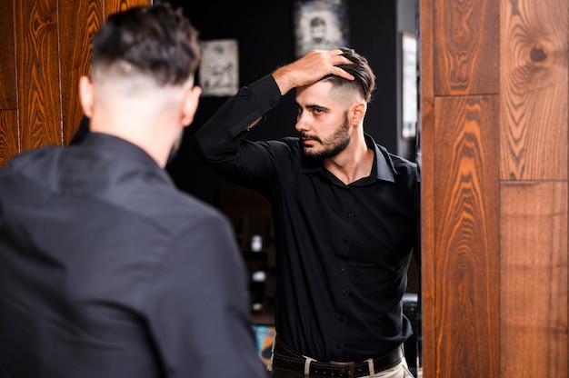 Hombre comprobando su nuevo corte de pelo en un espejo Foto gratis