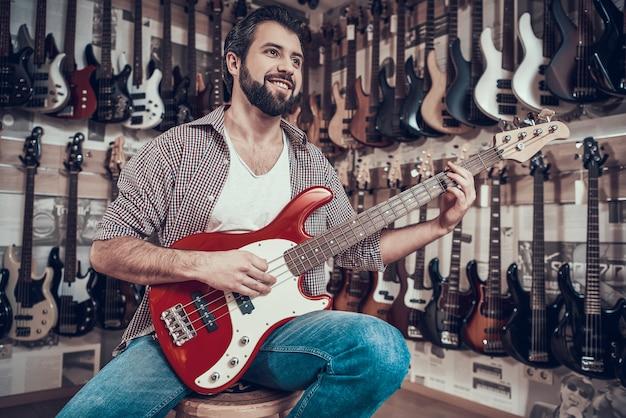 El hombre comprueba la guitarra eléctrica en la tienda de instrumentos musicales. Foto Premium