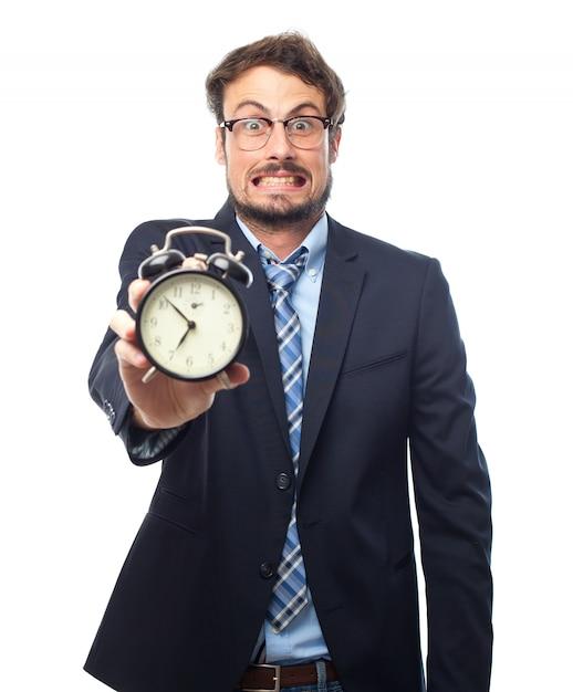 Hombre con traje sujetando un reloj despertador Foto Gratis
