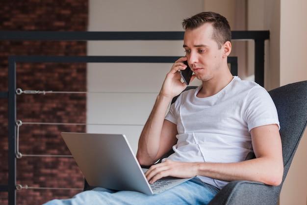 Hombre concentrado que habla en smartphone y que se sienta en silla con el ordenador portátil Foto gratis