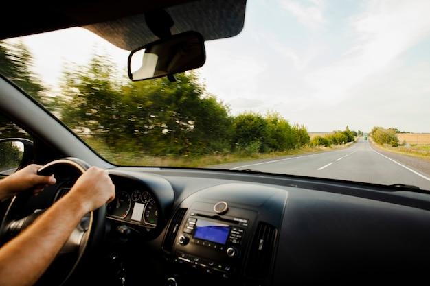 Hombre conduciendo un coche en carretera Foto gratis