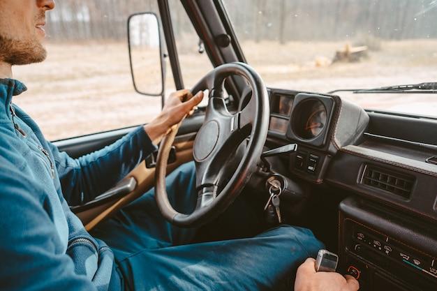 Hombre conduciendo suv coche por camino forestal Foto gratis