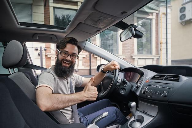 Hombre conductor feliz sonriendo mostrando los pulgares arriba conducir coche deportivo Foto gratis