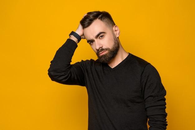 El hombre confiado hermoso peina el pelo aislado. Foto Premium