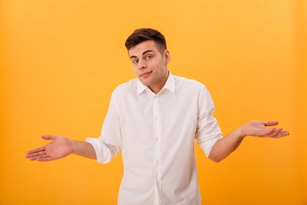 Hombre confundido con camisa blanca se encoge de hombros y mira a la cámara Foto gratis