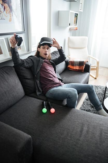 Hombre confundido sentado en casa jugar con gafas 3d Foto gratis