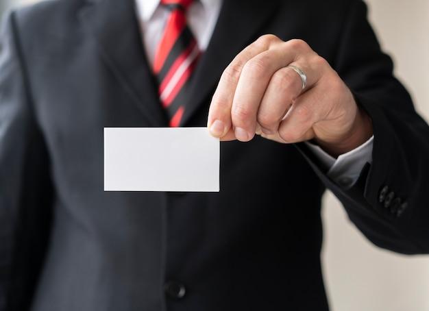 Hombre corporativo con tarjeta en blanco Foto gratis