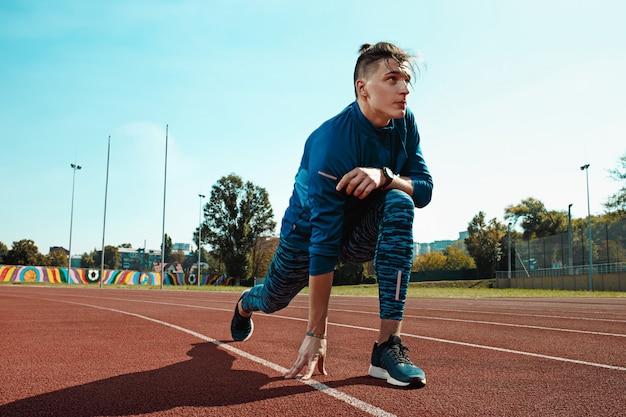 Hombre corredor estirando las piernas preparándose para correr entrenamiento en pistas del estadio haciendo calentamiento Foto gratis