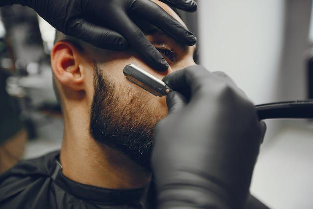 El hombre se corta la barba en la barbería. Foto gratis