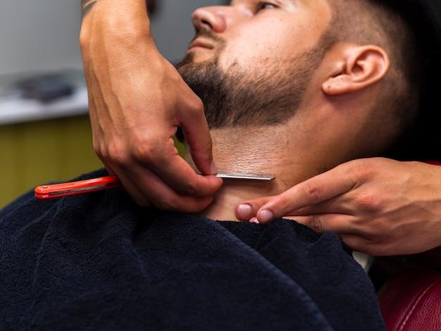 Hombre cortándose la barba Foto gratis
