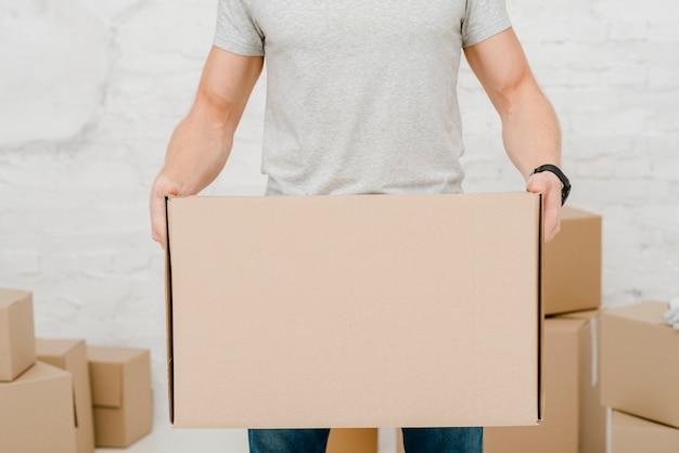 Hombre de cultivos con caja de cartón Foto gratis