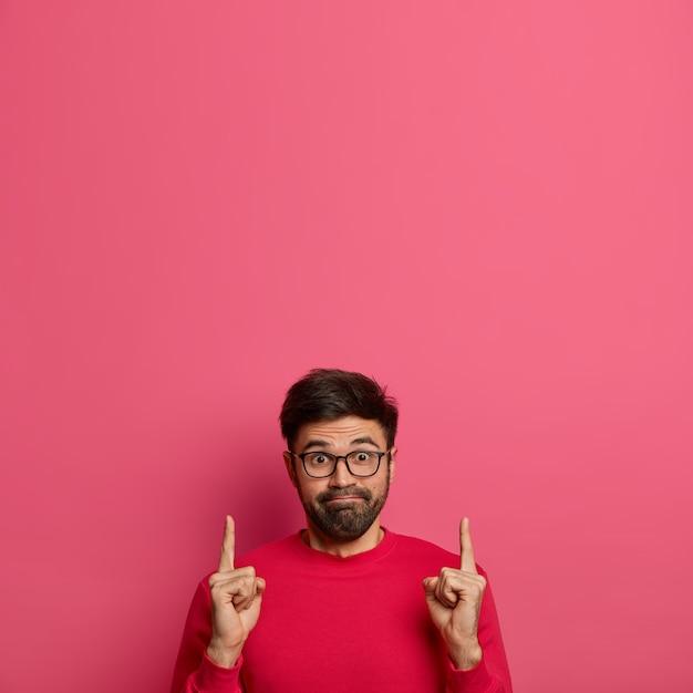 Hombre curioso impresionado presiona los labios, anuncia el producto, señala arriba con ambos dedos índices Foto gratis