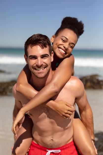 Hombre dando caballito a mujer en la playa bajo el sol Foto gratis