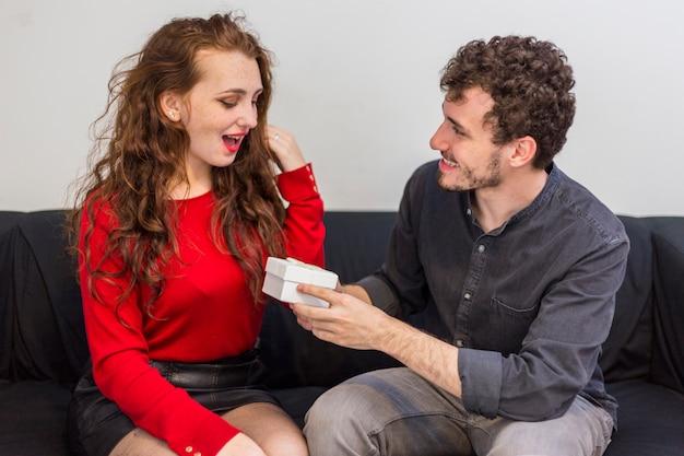 Hombre dando una pequeña caja de regalo a la mujer en el sofá Foto gratis