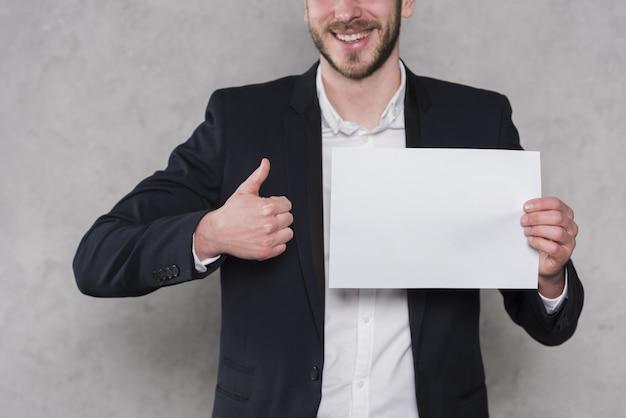 Hombre dando pulgares y sosteniendo papel en blanco Foto gratis