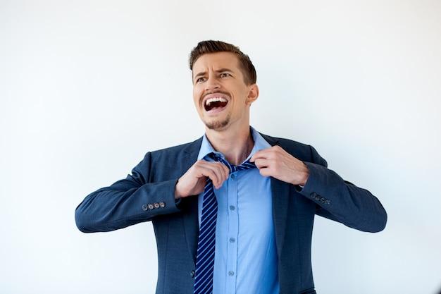 Hombre de negocios frustrado lazo desvinculación y gritando Foto Gratis