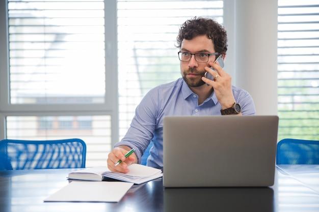 Hombre de negocios hablando por tel fono en la oficina for Telefono de la oficina