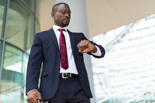 Hombre de negocios mirando su reloj de pulsera  20cd3c2265c3
