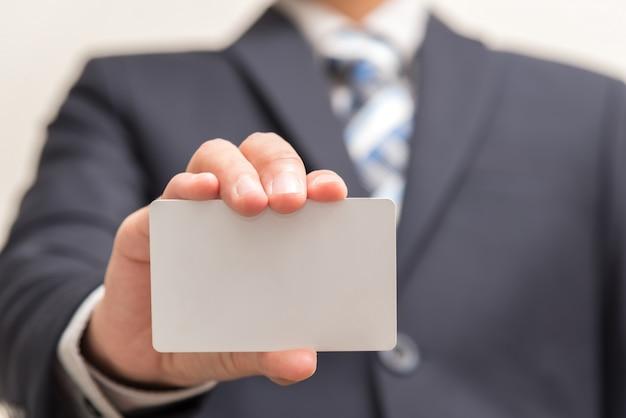 Hombre de negocios que sostiene la tarjeta en blanco blanca Foto Gratis