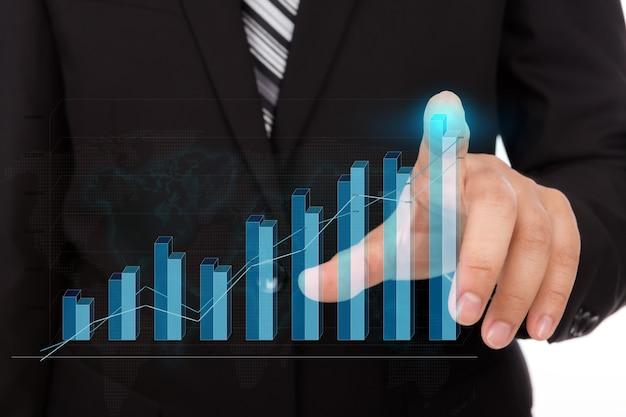 Hombre de negocios tocando la punta de un gráfico de barras Foto Gratis