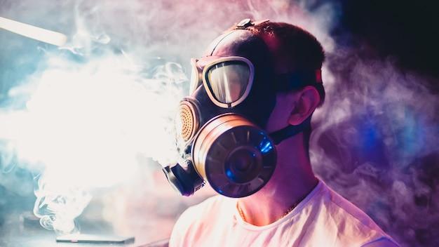 El hombre deja que las nubes de cachimba fumen en una máscara de gas Foto Premium