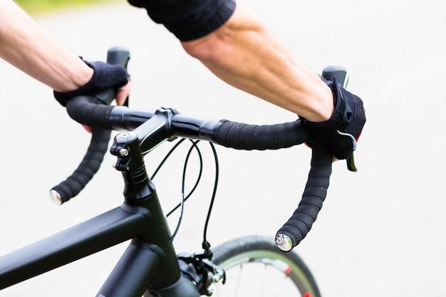 Hombre de deporte que tiene las manos en el manillar de bicicleta de carreras Foto Premium