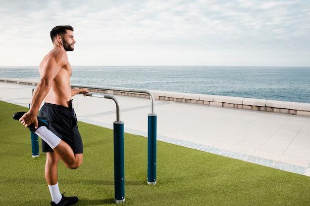 Hombre deportivo calentando antes del entrenamiento Foto gratis