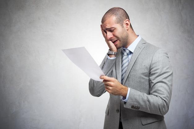 Hombre deprimido leyendo un documento Foto Premium