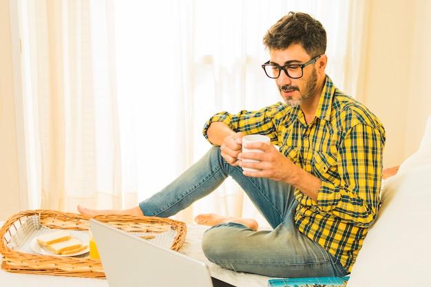 Hombre desayunando en la cama mirando portátil en el dormitorio Foto gratis