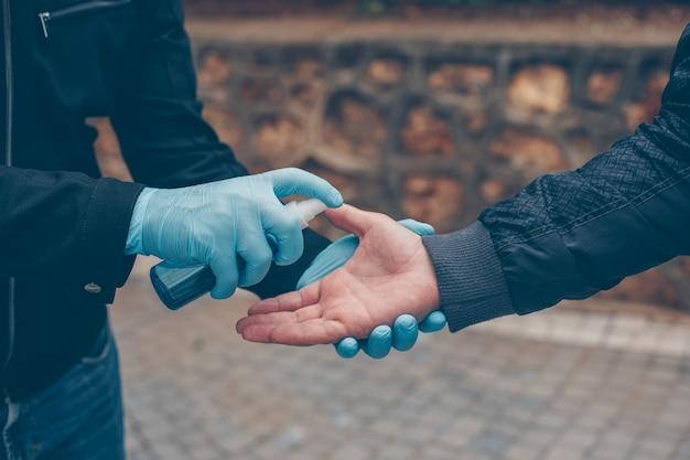 Un hombre desinfectando la mano de otro con guantes en el patio durante el día. Foto gratis