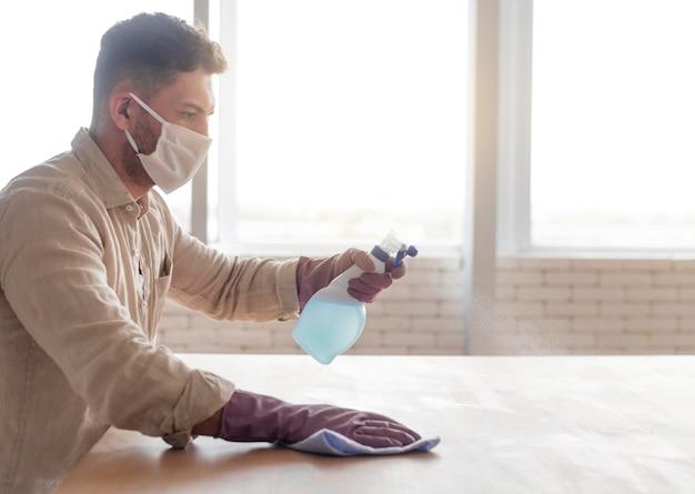 Hombre desinfectando la superficie de madera Foto gratis