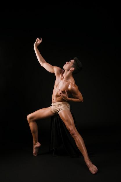 Hombre desnudo separando piernas y manos a los lados Foto gratis