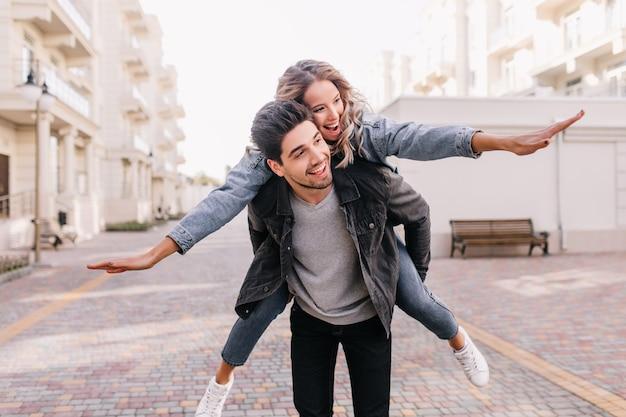 Hombre despreocupado de chaqueta negra caminando con chica. retrato al aire libre de la feliz pareja disfrutando juntos el fin de semana. Foto gratis
