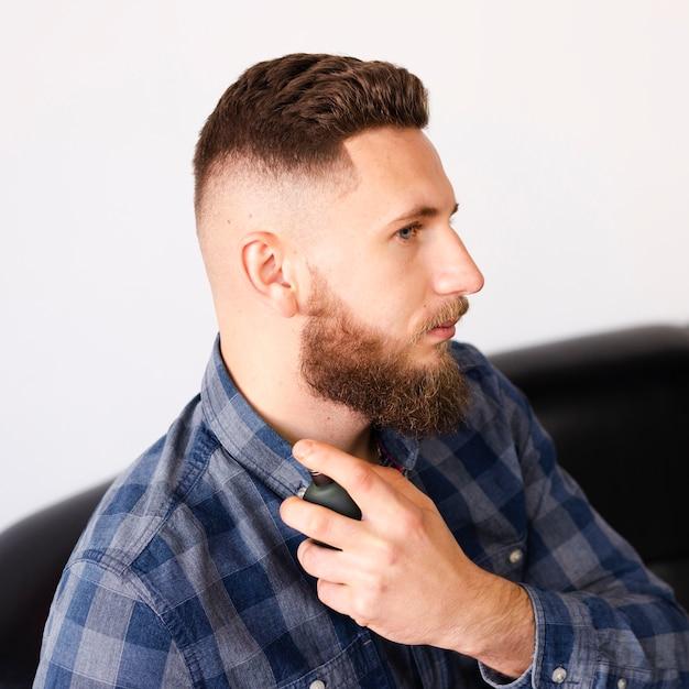 Hombre después de un corte de pelo fresco y cuidado de la barba Foto gratis