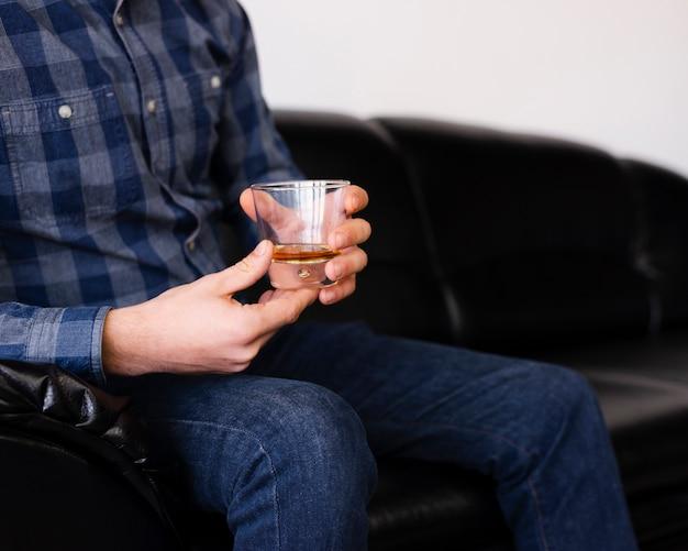 Hombre disfrutando de una bebida en la peluquería Foto gratis