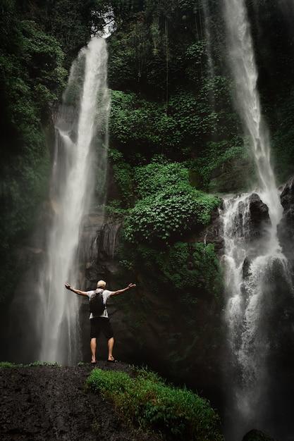 Hombre disfrutando de la cascada levantó las manos. viajes concepto de estilo de vida y éxito vacaciones en la naturaleza salvaje en la montaña y la selva. Foto Premium
