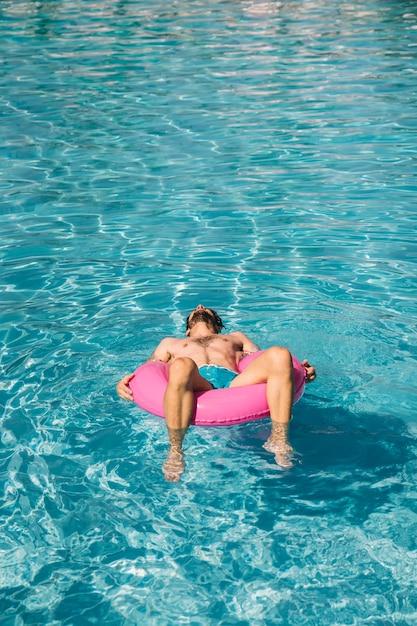 Hombre durmiendo en anillo flotador en piscina | Descargar Fotos gratis