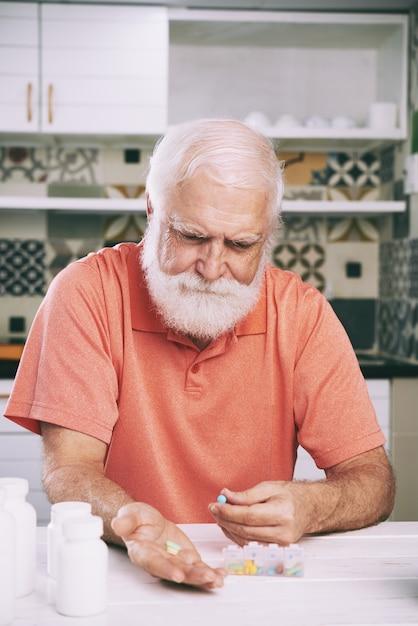 Hombre de edad tomando pastillas Foto gratis